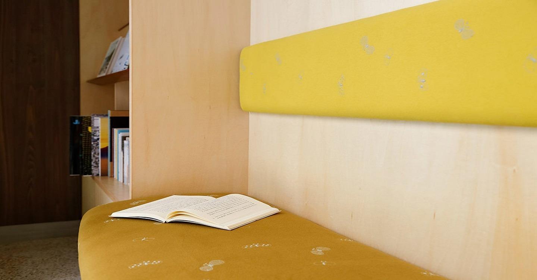 本棚の中にあるふたり並んで座れるベンチは、「ミナペルホネン」の「CHOUCHO」の生地。