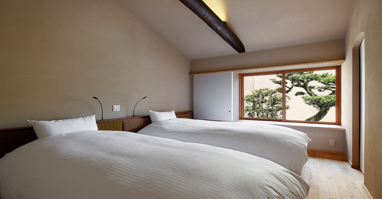 ヘッドボードは「ミナペルホネン」の「タンバリン」。ベッドにごろんと寝転ぶと、天井には立派な梁。150年にわたって、この京町家の屋根を支え続けてきた月日の長さを感じます。